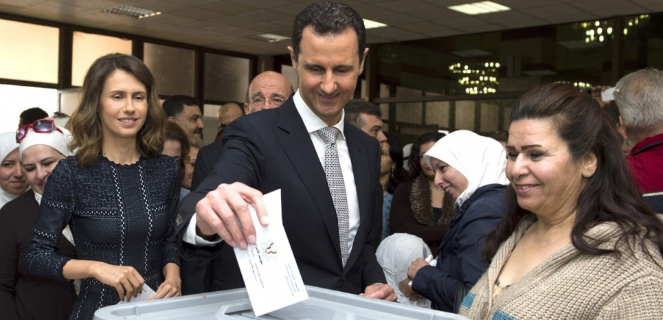 "A handout picture released by the official Syrian Arab News Agency (SANA) on April 13, 2016 shows Syrian President Bashar al-Assad (C) and his wife Asma (L) casting their votes at a polling station in Damascus during the parliamentary elections. Polls opened in areas of war torn Syria controlled by the president, for a vote that will not be recognised by the United Nations and has been dismissed by regime opponents as illegitimate. / AFP PHOTO / SANA / STR / == RESTRICTED TO EDITORIAL USE - MANDATORY CREDIT ""AFP PHOTO / HO / SANA"" - NO MARKETING NO ADVERTISING CAMPAIGNS - DISTRIBUTED AS A SERVICE TO CLIENTS =="