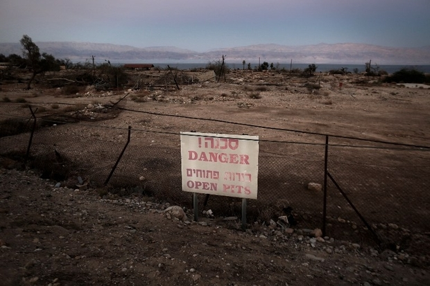 A general view shows a poster warning visitors of sinkholes in Israel's abandoned tourist resort of Ein Gedi on the shore of the Dead Sea on July 11, 2016. Experts have warned that the Dead Sea, the lowest and saltiest body of water in the world, is on course to dry out by 2050, with the emergence of sinkholes forcing the closure of roads and beaches, as well as damaging agriculture. / AFP PHOTO / MENAHEM KAHANA